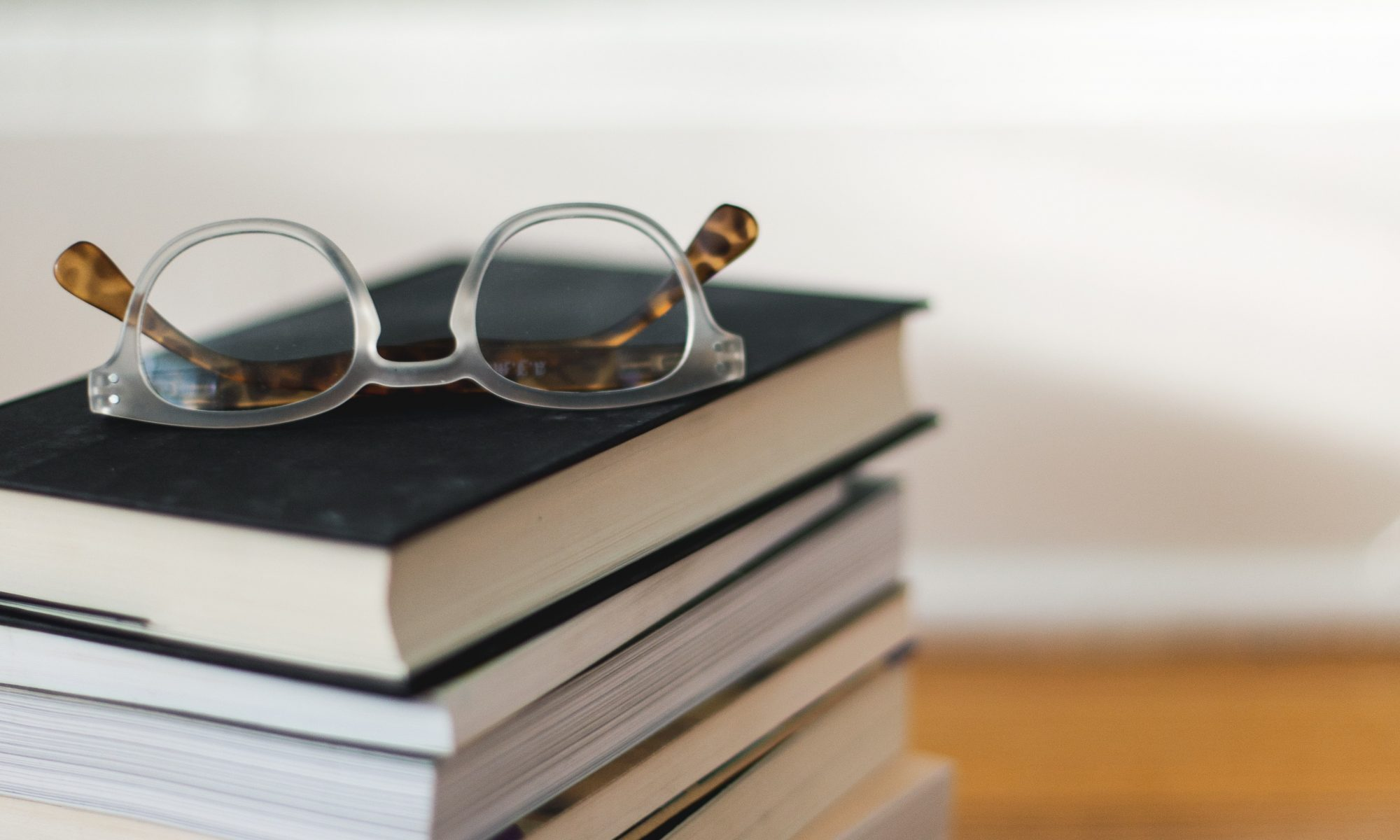 Stack of books with a pair of glasses on top.